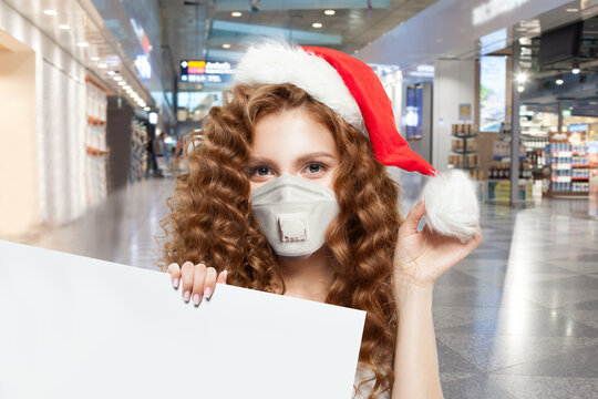 Pretty woman Santa in protective medical mask holding empty signboard in shopping mall. Christmas and New Year sale concept
