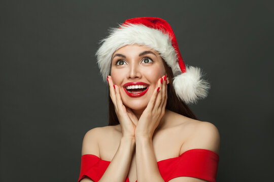 Excited surprised woman in Santa hat smiling on black. Christmas holiday and New Year party portrait