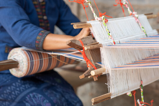 Close-up of women's hands weaving with traditional Thai weaving machine