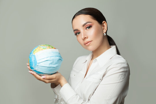 Caring woman holding globe earth in medical protective mask on gray background