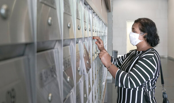 Woman wearing face mask opening metal letter box