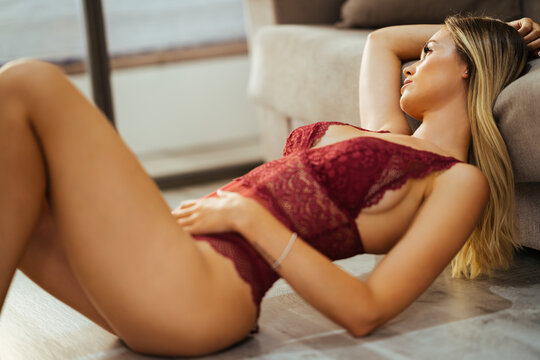 Young adult caucasian woman in red lingerie lying on the floor