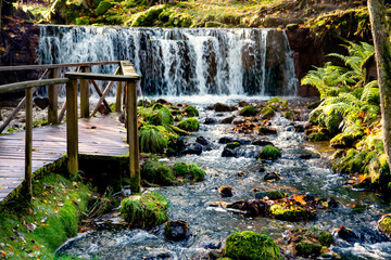 Small waterfall with a rocky river and a small wooden bridge on a sunny autumn day in Latvia