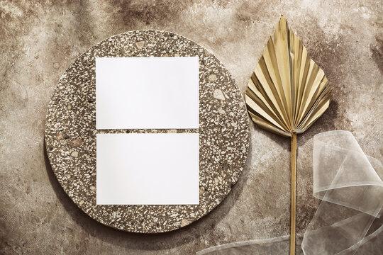 Feminine wedding invitation card. Blank paper cards mockup, dry palm leaf, granite elements and ribbon. Beige grunge background. Modern stationery minimal scene. Top view, flat lay.