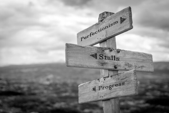 perfectionism stalls progress text quote on wooden signpost outdoors in black and white.