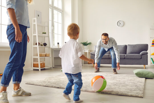 Happy young dad, mum and little son playing football with inflatable ball in living-room