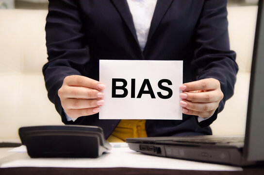 the word bias is written on a white piece of paper held by a business woman. personal opinions prejudice bias concept,