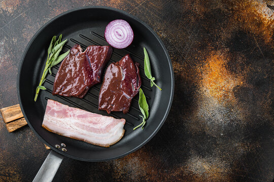 Raw beef liver sliced with bacon on grill pan over rustic background, flat lay with copy space