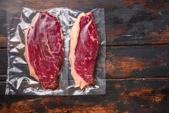 Picanha beef steak for sous vide cooking on dark old wooden table, top view space for text.