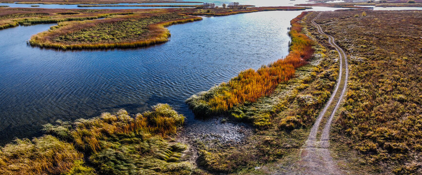 Aerial panoramic landscape view over river with islands of growing reeds, gravel road on embankment, autumn evening, Samara, Russia
