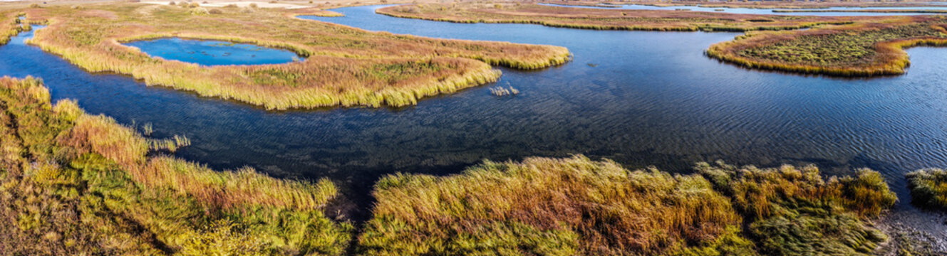 Aerial panoramic landscape view over river with islands of growing reeds, autumn evening, Samara, Russia