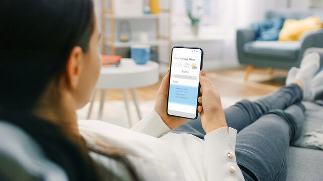 Young Woman at Home Uses Smartphone for Checking Weather Predictions and Coming Day Plans in Daily Schedule Calendar. She's Sitting On a Couch in Her Cozy Living Room. Over the Shoulder Shot