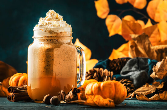 Pumpkin spiced latte or coffee in glass jar on blue table. Autumn or winter hot drink in festive natural table setting with orange leaves, spices, small pumkins, pine cones