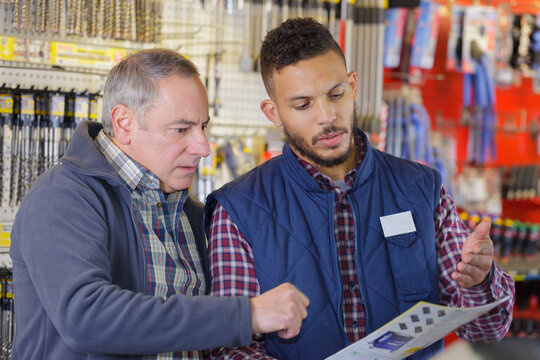 two men looking through catalogue in hardware store