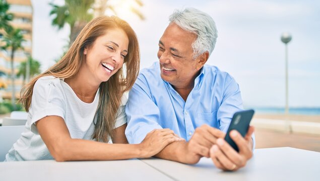 Middle age couple in love sitting at the terrace of coffee shop using smartphone happy and cheerful together