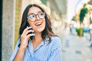 Photo sur Plexiglas Dinosaurs Young hispanic businesswoman smiling happy talking on the smartphone at the city.