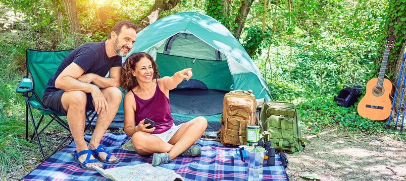 Middle age couple  of hiker smiling happy camping at the forest. Sitting on the floor using smartphone pointing with finger to the sky