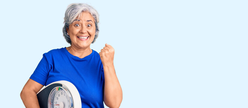 Senior woman with gray hair holding weight machine to balance weight loss screaming proud, celebrating victory and success very excited with raised arms