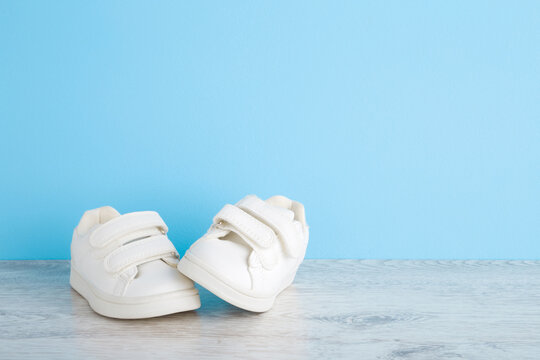 New white sport shoes for little kid on wooden floor at light blue wall background. Pastel color. Baby footwear. Empty place for text. Front view. Closeup.