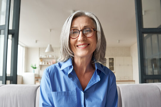 Smiling mature 60s middle aged woman looking at web camera video conference calling in virtual web chat remote business meeting by social distance remote videocall. Headshot face portrait. Webcam view