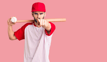 Young handsome man with beard playing baseball holding bat and ball pointing with finger to the...