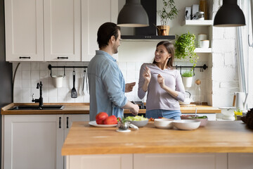 Playful young married couple dancing to energetic music in modern kitchen, distracted from preparing healthy food in modern kitchen. Happy millennial family spouses having fun, enjoying weekend time.