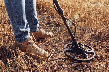 Obraz Man with metal detector equipment searching for metal goods in the field - fototapety do salonu