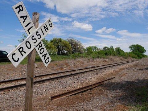 Medium wide shot of a crossing sign at a railroad track