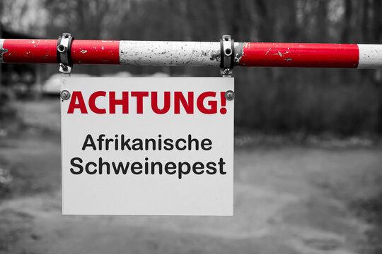 """Schild mit der Aufschrift """"Achtung Afrikanische Schweinepest"""" an einer Schranke"""