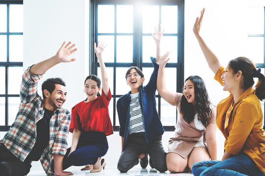 Cheerful asian male and female students celebrating winning in college contest giving high five, emotional multiracial members of crew excited with success in productive working process on startup