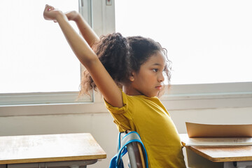 African American school girl stretching with arms raised in classroom, education, learning....