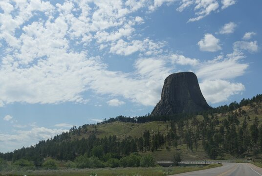 Winding road with the Devils Tower in Wyoming, America's first national monument, seen on a beautiful day.