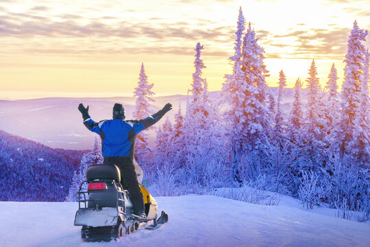 Man driving snowmobile in snowy forest. Concept freedom in winter travel.