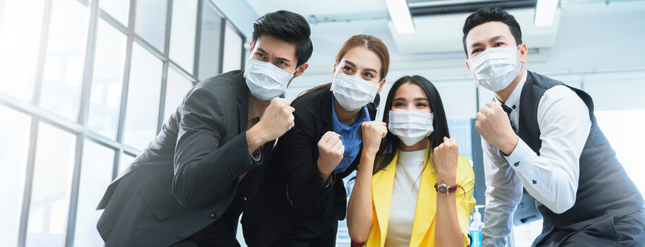 portrait of young asian businessman and businesswoman wearing corona virus face mask  hand rise empower hand gesture successful achievement concept