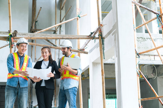Young Asian engineers teamwork site inspector and discuss together using notebook computer and paper blueprint at building construction site.home renovation ideas concept