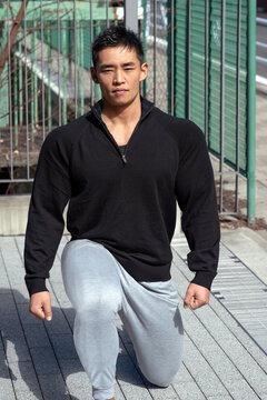 A young Asian clothed bodybuilder poses outdoors