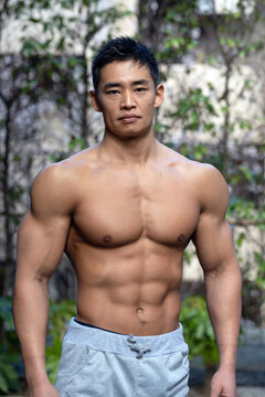 A young Asian bodybuilder poses shirtless outdoors showing off a muscular torso