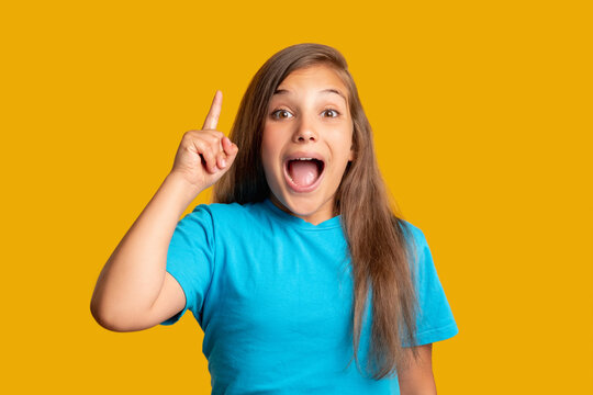 Great idea. Astonished child. Aha moment. Opportunity discovery. Excited happy young girl in blue t-shirt pointing up isolated on orange copy space background.