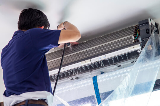 The technicians are cleaning the air conditioner by spraying water. Hand and water spray are cleaning the air conditioner. Focus at air conditioner.