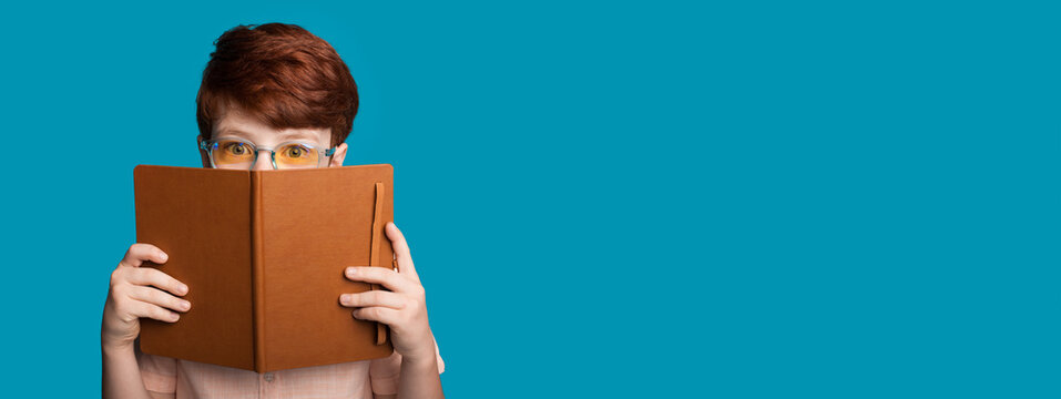 Ginger boy with glasses is hiding behind a book looking at camera on a blue studio wall with free space
