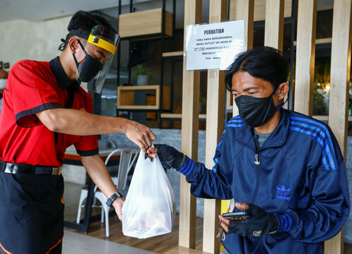 A waiter wearing a face shield and a protective mask hands takeaway food to a man at a restaurant, in Jakarta