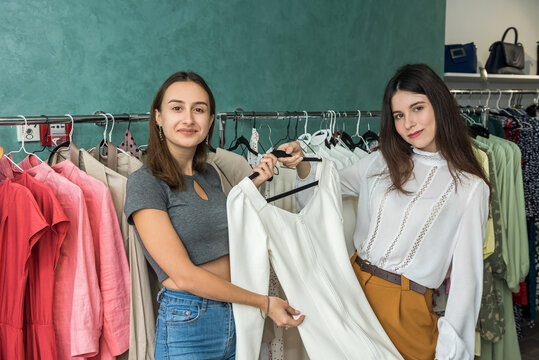 Two friends choosing a new cloth in a clothing boutique