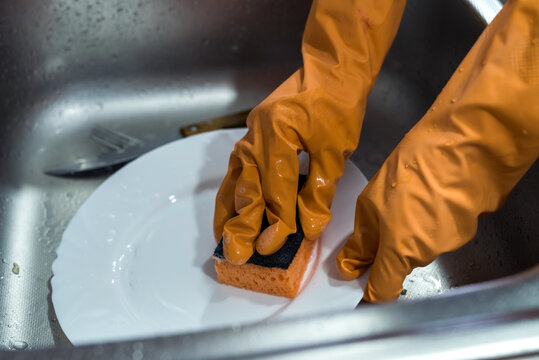 Female hand in gloves washing dishes over the sink in the kitchen