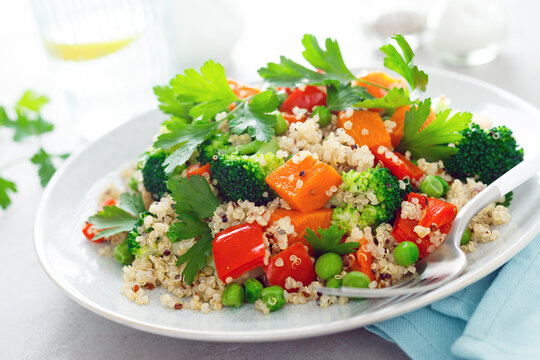 Quinoa and broccoli vegetable salad with baked butternut squash or pumpkin, green peas, bell pepper and parsley