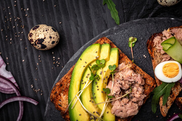Tuna sandwiches with avocado and microgreen on wholemeal bread, wooden background. Tasty tuna sandwiches for breakfast. Healthy snack. Top view, flat lay