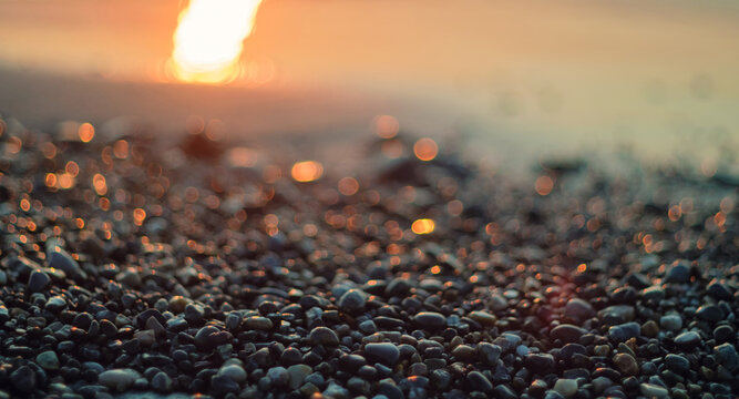 Close-up view of a pebble beach with blurred sea and sun background, selective focus