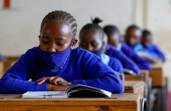 A schoolgirl wears a face mask as she reads a book inside a classroom at the Olympic Primary School during the partial reopening of schools, in Nairobi