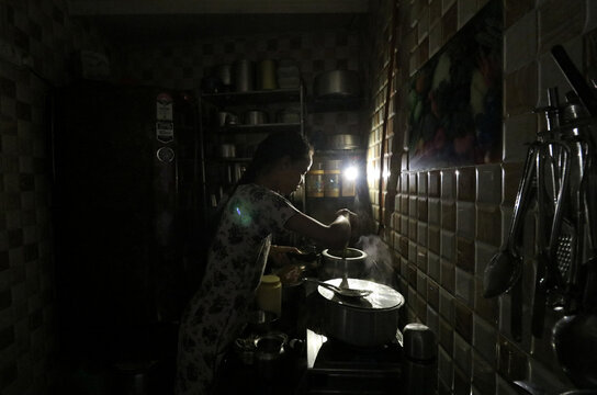 A woman uses her mobile phone torch as she cooks food inside her kitchen during a power outage in Mumbai
