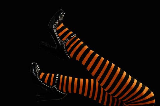 Female legs in orange stockings waving in the air.