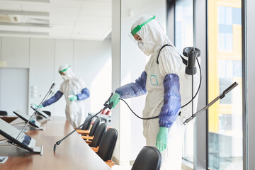 Photo sur Plexiglas Dinosaurs Side view portrait of two workers wearing hazmat suits disinfecting conference room in office, copy space